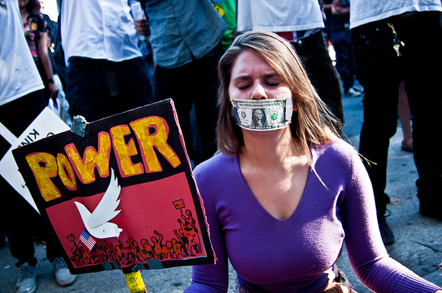 A woman with a dollar bill taped over her mouth, holding a sign that says