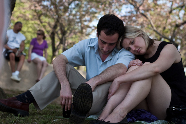 Two couples in a park. One sitting on a rock, and one resting against each other on the ground