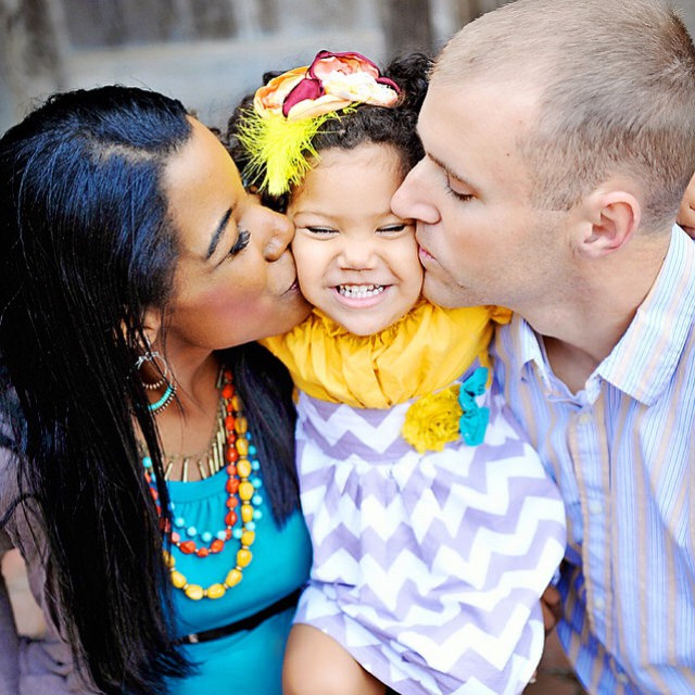A white man and a black woman kissing their daughter