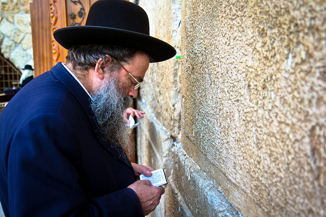 A jewish man placing his prayer note in a wall