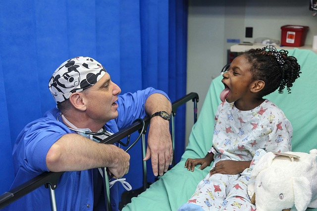 A white doctor being goofy with a black girl patient