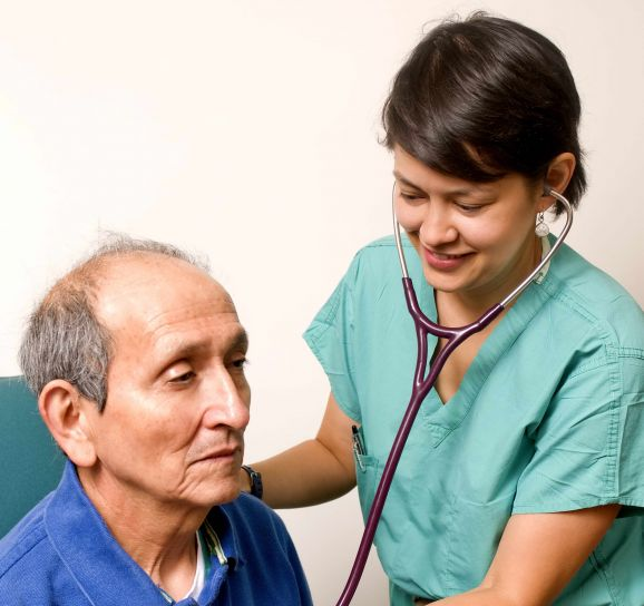 A nurse checking the heart rate of an elderly man