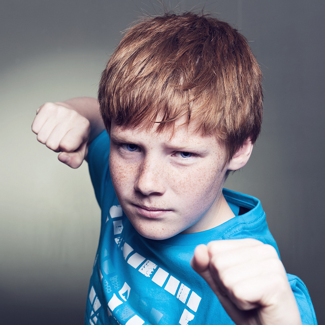A young boy posed with his fists up, ready to fight