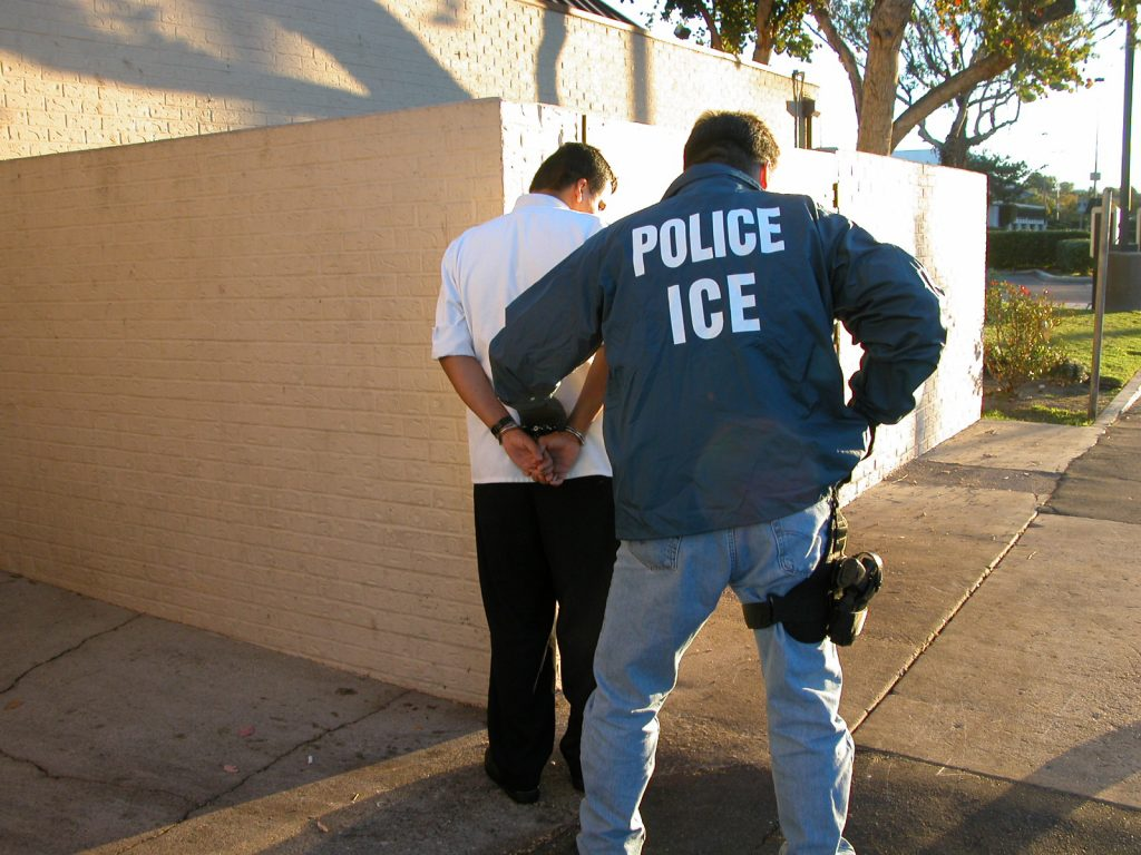 A cop arresting a man outside a building