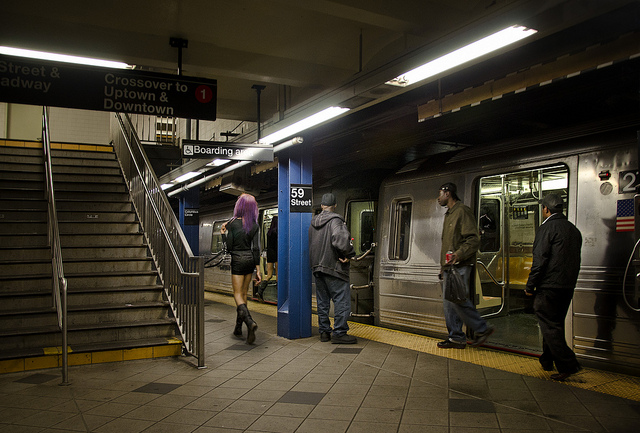 A prostitute standing next to a platform at the subway station
