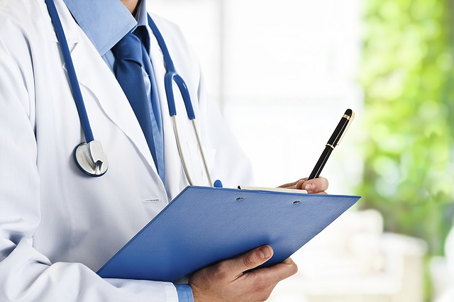 A doctor holding his pen to his clipboard