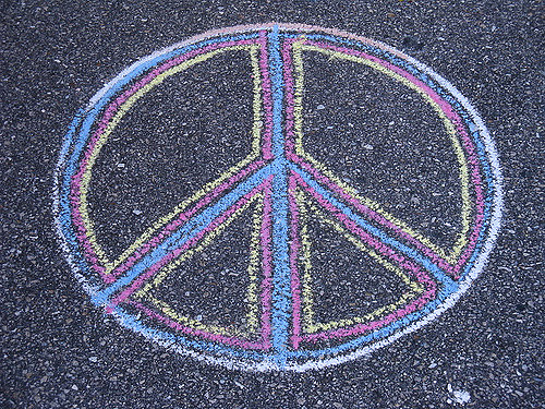An International Peace Symbol drawn with multicolored chalk on a blacktop