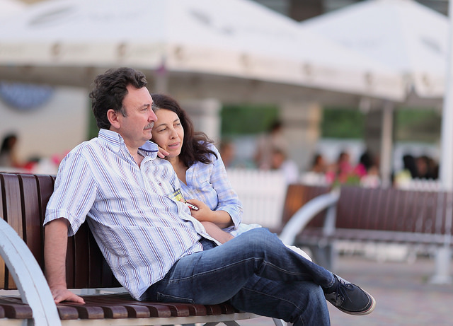 A woman leaning against her boyfriend on a public bench