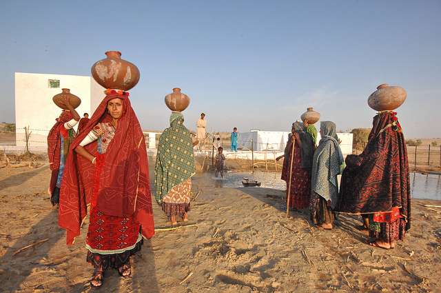 Women with bowls on their head to fill up with water gathered at the Somo Samo village well
