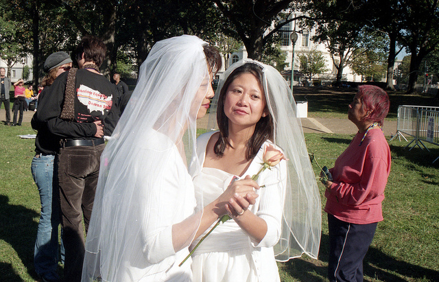 Two women in wedding dresses who have just been happily married