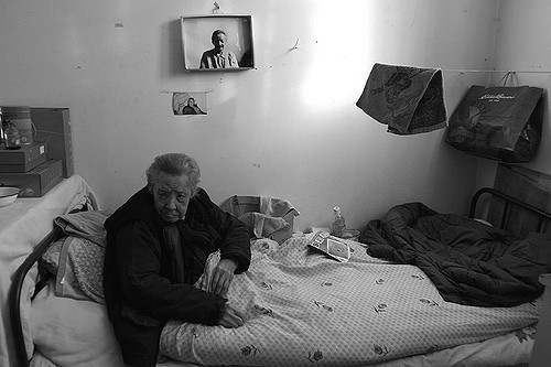 An elderly woman looking sad inside of a nursing home