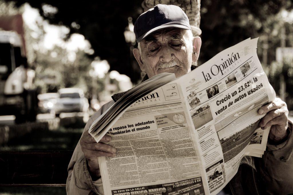 An old man reading a newspaper