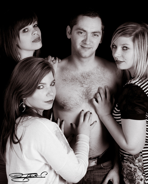 A man posing shirtless with three women who have their hands all over him