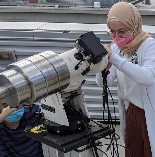 A student recalibrates the telescope.